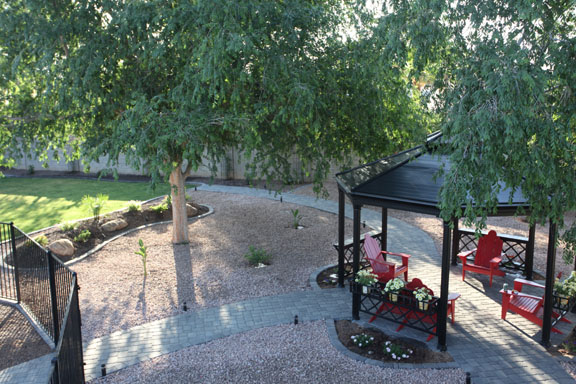 Backyard landscape design with paver patio, gazebo, grass, plant areas, and BBQ pad